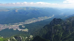 Tilt from Caraiman Peak to Bucegi city, aerial flight, Romania Stock Footage