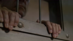 HANDS & FACE IN THE WINDOW OF A CELL DOOR Stock Footage
