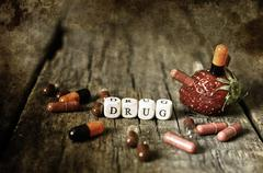 Old shabby filthy Photo drug pill on wooden table concept addict Stock Photos