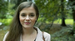 Face of beautiful young woman against green city park Stock Footage