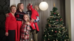 Happy family on Christmas Eve by Xmas tree Stock Footage