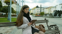 Woman working on tablet sitting on bench in old town Stock Footage