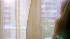 The girl looks out the window and waves on a Sunny day Stock Footage