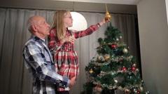 Sweet little girl adjusting Christmas tree top Stock Footage