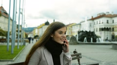 Woman sitting on bench in old town making phone call Stock Footage