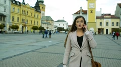 Woman walking outdoors in old town making phone call Stock Footage
