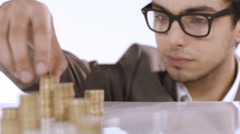 Sharing the success, young man stacking coins Stock Footage