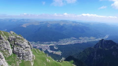 Caraiman Peak, aerial view of hikers and Bucegi city, Romania Stock Footage