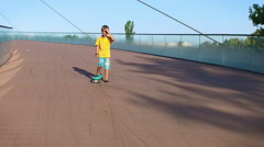 Child cruising, down a bridge on a pennyboard, slow motion Stock Footage