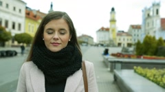 Woman in autumn coat standing outdoors in old town Stock Footage