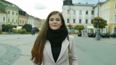 Woman in autumn coat walking outdoors in old town Stock Footage