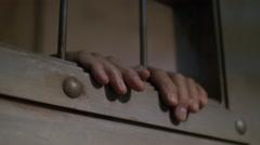 HANDS IN THE WINDOW OF A CELL DOOR Stock Footage