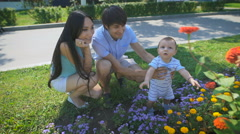 Family looking at a flower bed with flowers Stock Footage