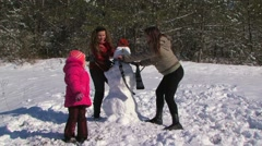 Family of four run around upside down snowman at winter day Stock Footage