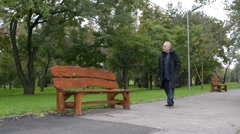 Old man during a walk in the park - day time Stock Footage