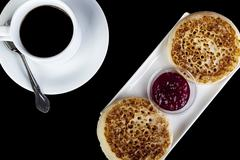Fresh crumpets on a rectangular serving plate with black coffee Stock Photos