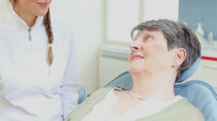 Smiling elderly woman talking with dentist Stock Footage