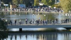 4K people walking on lake bridge Olympia Park Munich Germany Europe Stock Footage