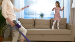 Housewife dancing with a vacuum cleaner. Her little daughter jumping on couch. Stock Footage