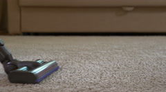A woman uses a vacuum cleaner to clean the carpet. Stock Footage