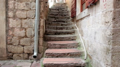 Narrow stone stairs are between ancient dwelling houses in old town of Kotor Stock Footage
