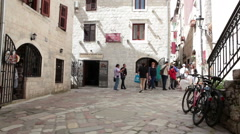 Visitors walk inner courtyards and narrow passes in area of old town of Kotor Stock Footage