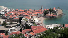 Peninsula with old walled fortifications of Budva city with urban sandy beach Stock Footage
