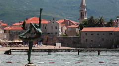 The Dancing Girl statue is on stones against Old Budva town and fortress.  Stock Footage