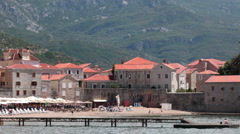 Camera review of Budva resort coast with sandy beach and old walled fort Stock Footage