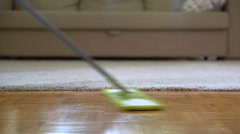 Woman cleaning parquet floors in the living room. Close-up. Stock Footage