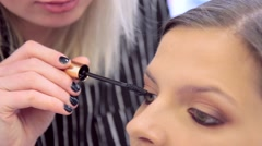 Make-up artist applying the mascara to model сlose-up. Stock Footage