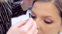 Pretty model's face and make-up artist hands with mascara Stock Footage