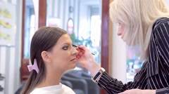 Make-up artist applying the eyebrow pencil to model's makeup Stock Footage