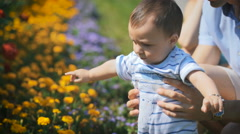 Father holds the child and shows him a flower bed with flowers Stock Footage