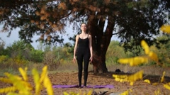 Beautiful female making yoga in forest. Copy space text Stock Footage