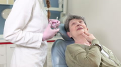 Smiling elderly woman giving high-five to dentist Stock Footage