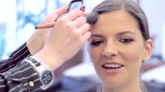 Makeup artist corrects models facial contours with blush Stock Footage