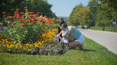 Mother and child looking at flowers in the flower bed Stock Footage