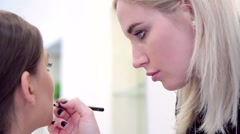 Make-up artist applying lip pencil to model close-up Stock Footage