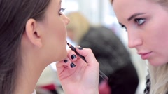 Model and make-up artist at work with lip pencil Stock Footage