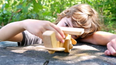 Boy playing with wooden toy airplane on a table outdoors Stock Footage