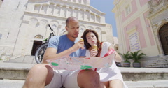 4K Happy couple sightseeing in the city looking at map & eating ice creams Stock Footage