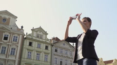 Young elegant woman takes pictures of the Old Town Square in Prague Stock Footage