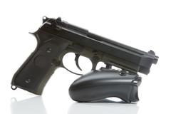 Hand gun over game controller - close up studio shot. Virtual and real life c Stock Photos