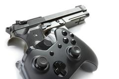 Game controller over a real handgun - close up studio shot. Virtual and real  Kuvituskuvat