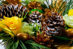 Christmas decoration with golden fir cones and silk roses Stock Photos
