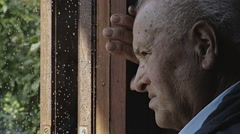 Sad depressed lonely man looking outside the window after the rain: hopeless man Stock Footage