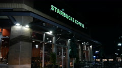 Night shot of store front at Starbucks entrance on raining day Stock Footage