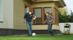 Boy Playing football with his Father on Backyard Stock Footage