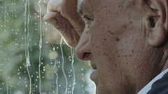 Depressed old man looking the rain falling on the window: sad lonely old man  Stock Footage